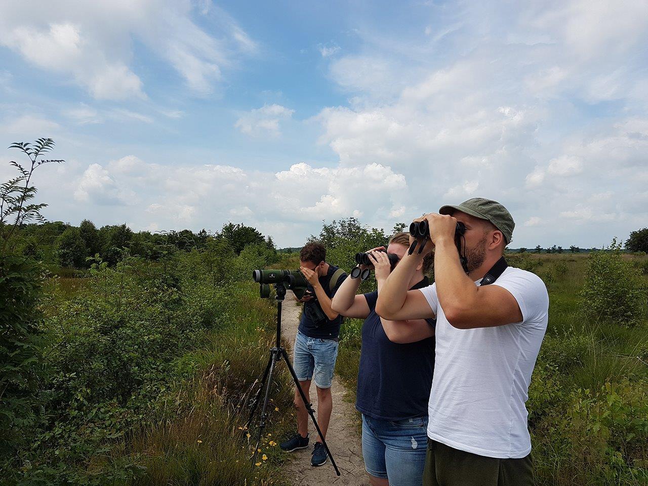 Deelnemers kijken naar de Kraanvogels langs de waterkant